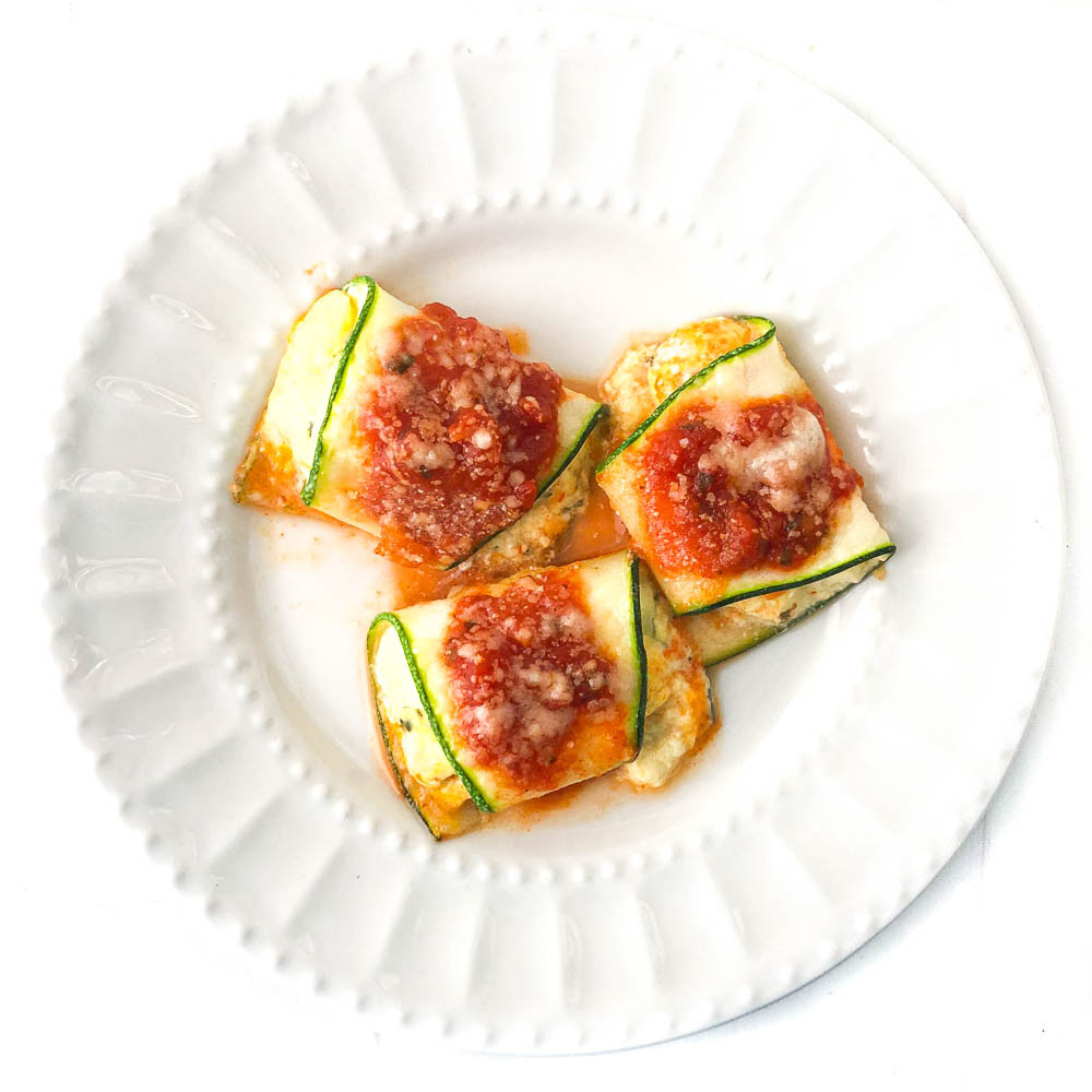 white plate with 3 cheese filled zucchini ravioli roll