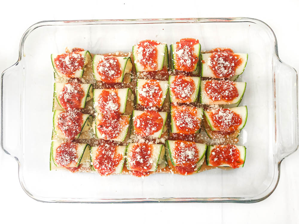 raw keto zucchini ravioli with sauce and cheese on top ready to bake