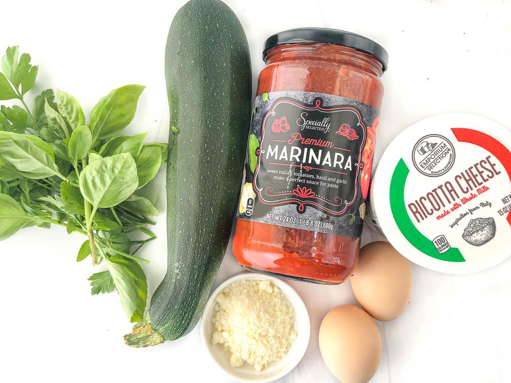 ingredients for zucchini roll ups - fresh herbs, zucchini, parmesan cheese, jar of marinara, ricotta and eggs