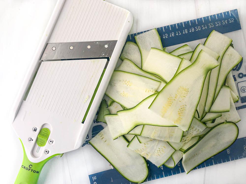 hand mandoline and sliced zucchini and cutting board