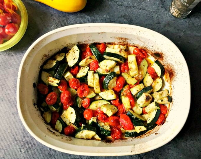white baking sheet with roasted zucchini and tomatoes