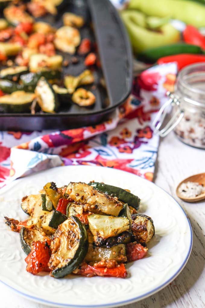 white plate with roasted zucchini and tomatoes low carb side dish and baking sheet in background