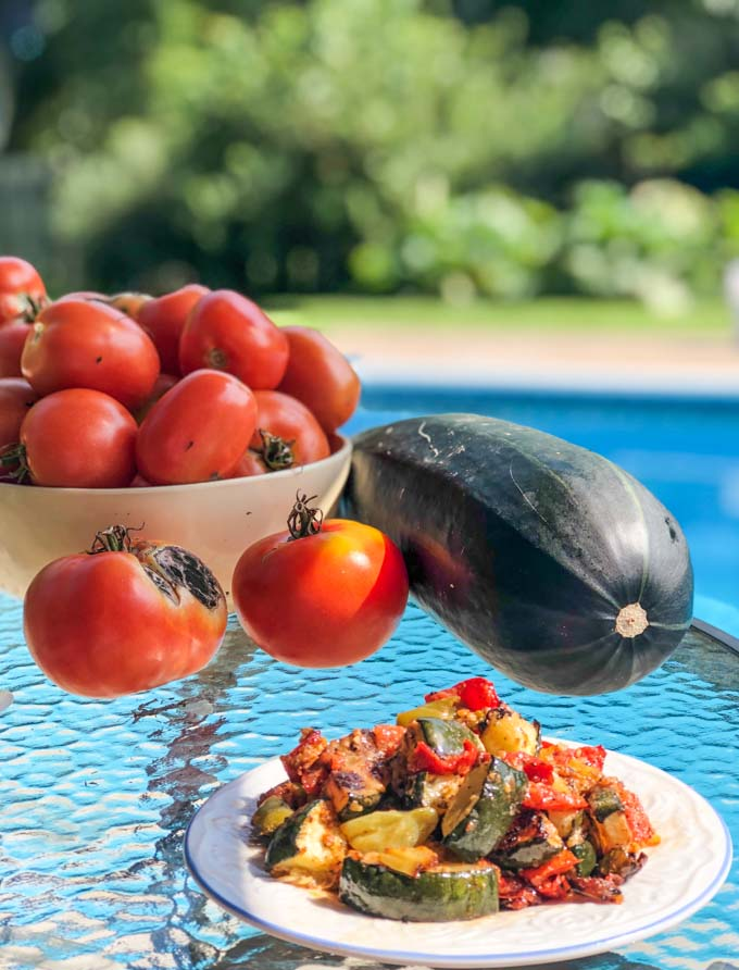 table with fresh tomatoes and zucchini from garden with pool and trees in background