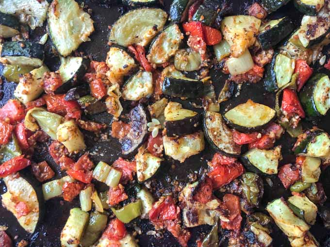 closeup of cookie sheet with roasted zucchini and tomatoes out of the oven