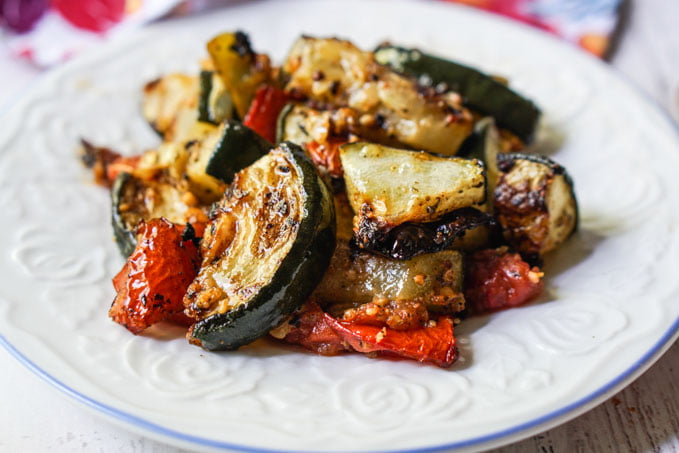 white plate with roasted zucchini and tomatoes low carb side dish
