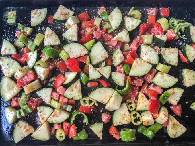 cookie sheet with raw zucchini, tomato and peppers with seasoning ready to go in oven
