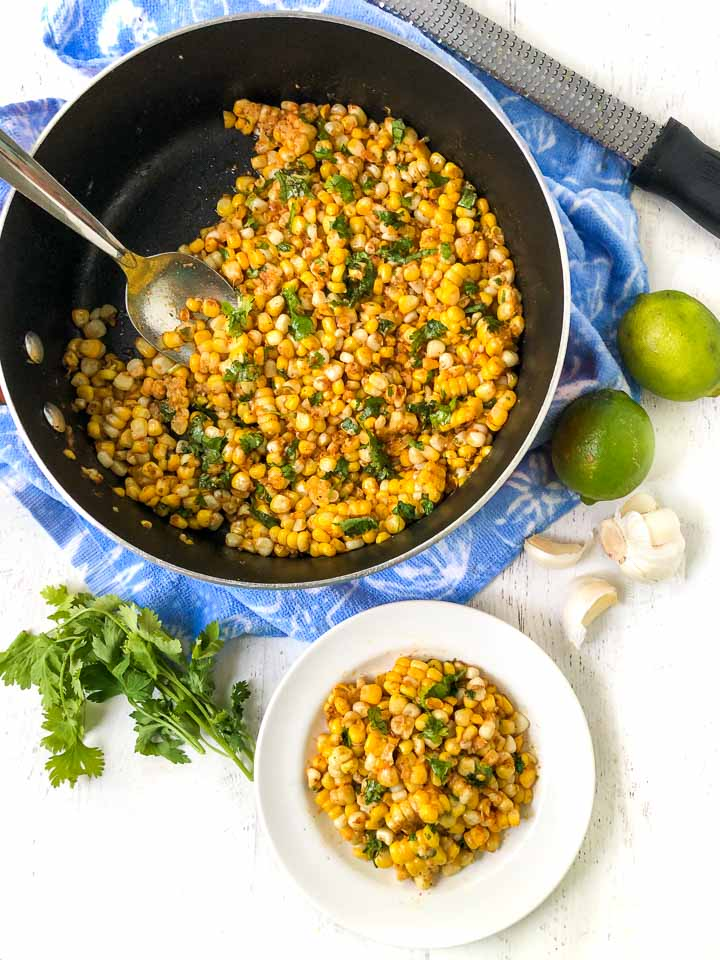 large pan with a bright blue towel underneath filled with Mexican corn, a zest and fresh limes, a bunch of cilantro and garlic