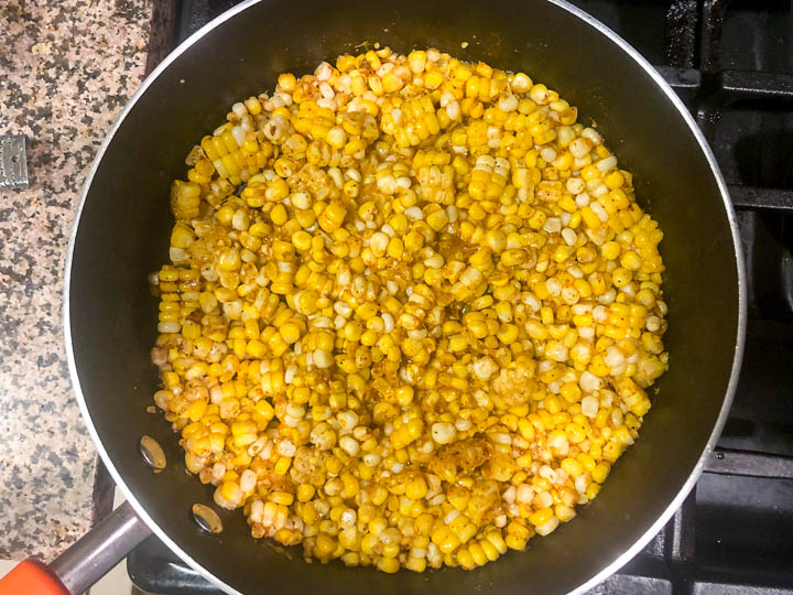 large pan on the stove with the corn and spices cooking