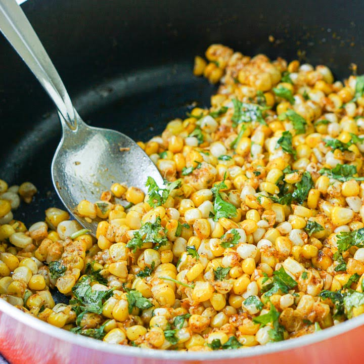 closeup of an orange pan with spicy Mexican corn with cilantro and a big spoon