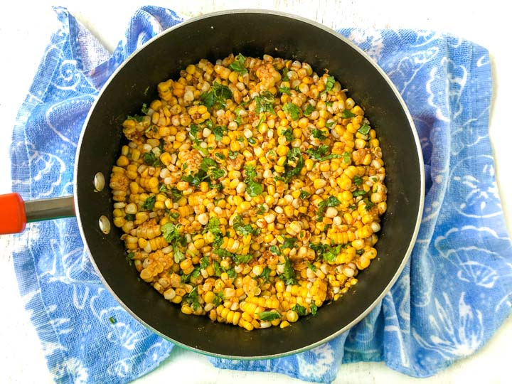 skillet with spicy Mexican corn with blue cloth underneath
