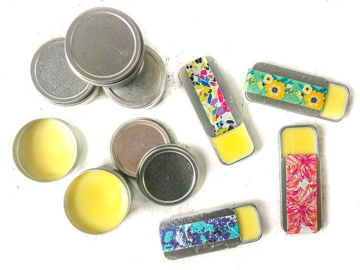 4 sliding tin containers with lip balm in it and 5 round tins with lip balm