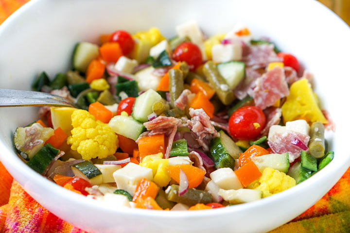 closeup of white bowl with color chopped vegetables, cheese, salami and pickles
