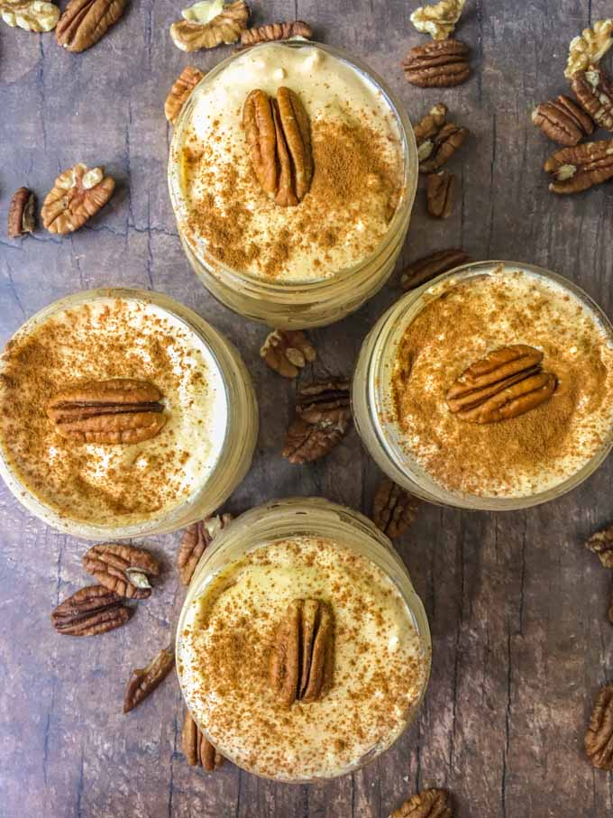 aerial view of keto no bake pumpkin cheese cake in a jar with pecans on top and scattered around