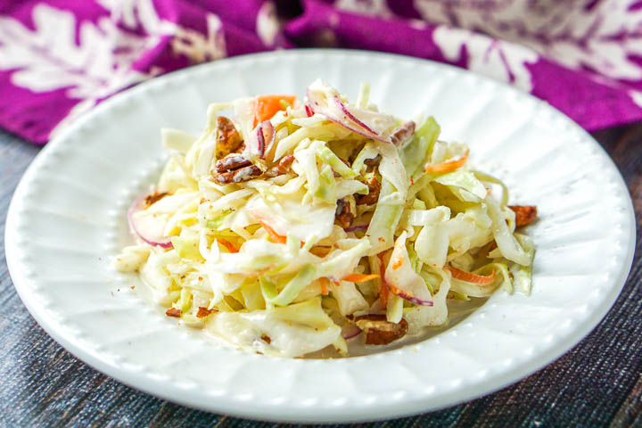 a closeup of a white plate of creamy southwestern coleslaw