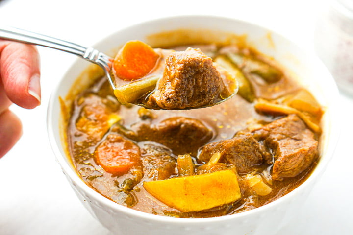 a spoonful of stew with a piece of carrot and a chunk of beef