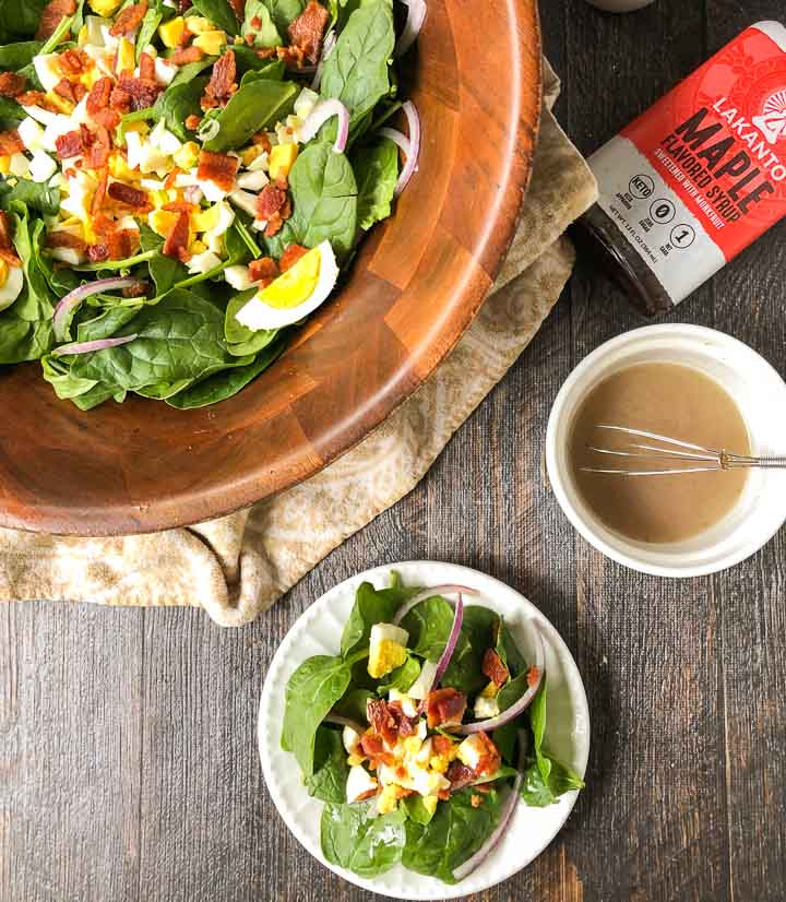 white plate and large wooden bowl with low carb spinach salad and a ramekin of hot maple bacon dressing and wooden bowl in background