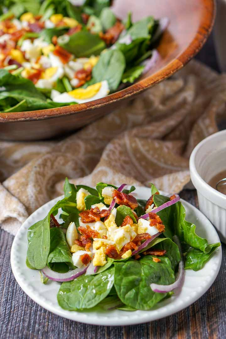 white plate with low carb spinach salad with hot maple bacon dressing and wooden bowl in background