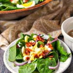 white plate with serving of spinach salad with low carb hot maple bacon dressing and text
