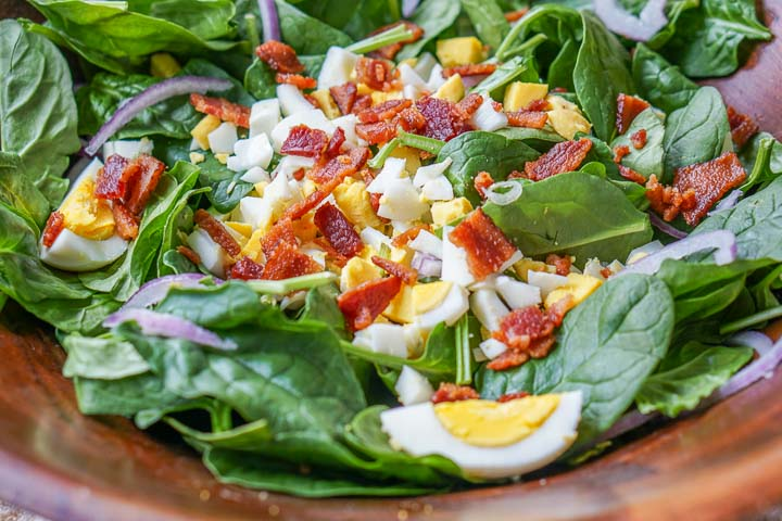 big wooden bowl with classic spinach salad dressed in low carb hot maple bacon dressing