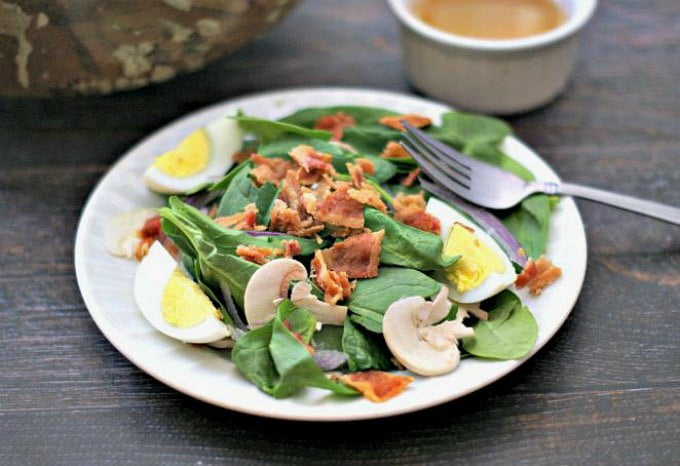 This is a classic spinach saladwith hot maple bacon dressing. Bacon, eggs and veggies topped with the warm, salty and sweet dressing to make the perfect fall salad that is low carb and Paleo too!