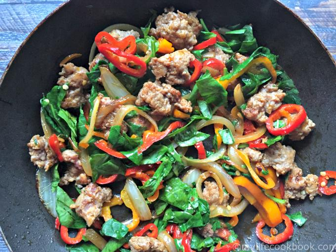 skillet with sautéed onions, peppers, sausage and spinach