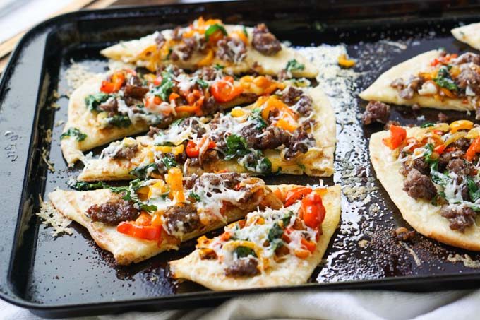 cookie sheet with asiago, sausage and pepper flatbread pizza cut up