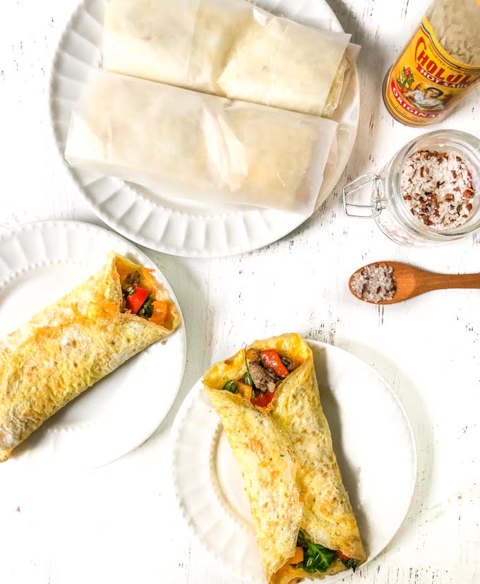 white plates with keto egg wrap breakfast burritos with salt and wooden spoon