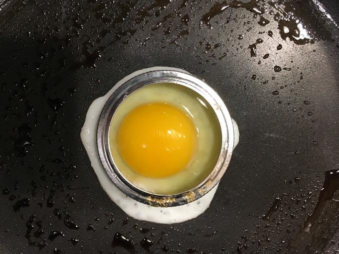 egg inside a mason jar lid in a skillet