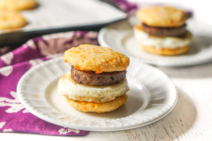two white plates with egg and sausage sandwich