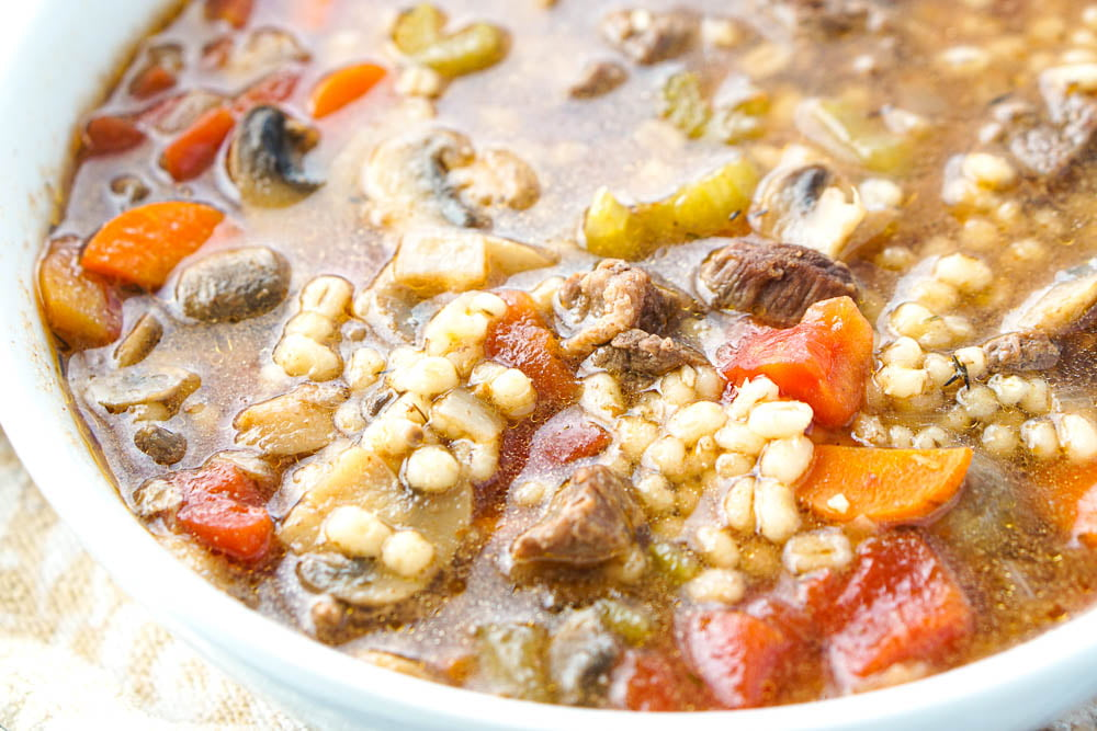 closeup showing pearl barley, beef and veggies in the soup