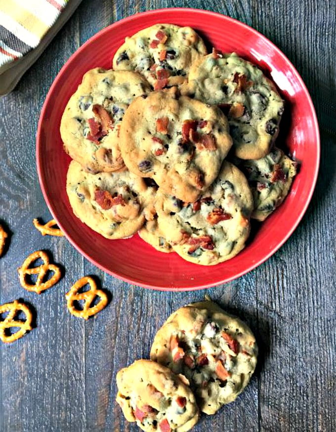 red plate with chocolate chip cookies and with pretzels scattered nearby
