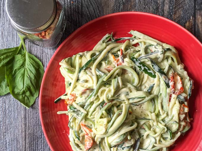 These easy creamy sun dried tomato & basil zoodles only take 15 minutes to make. The zucchini noodles have a creamy garlic, basil and sun dried tomatoes sauce that is decadent and delicious.
