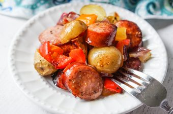 white plate with kielbasa, potatoes and peppers