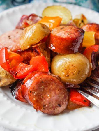white plate with kielbasa, potatoes and peppers