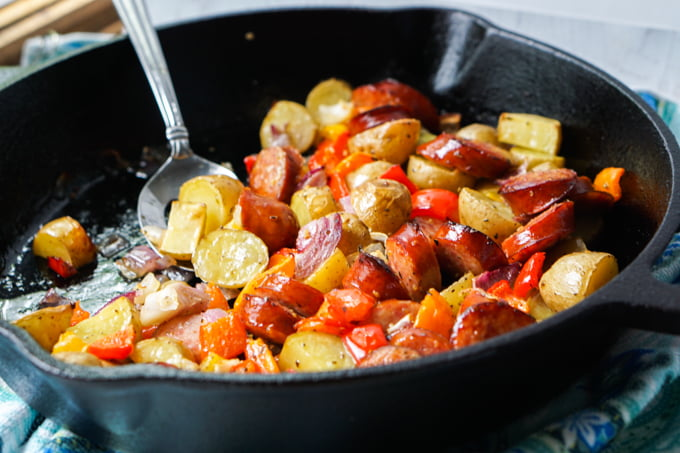 cast iron skillet with cooked potatoes, peppers and kielbasa with a spoon