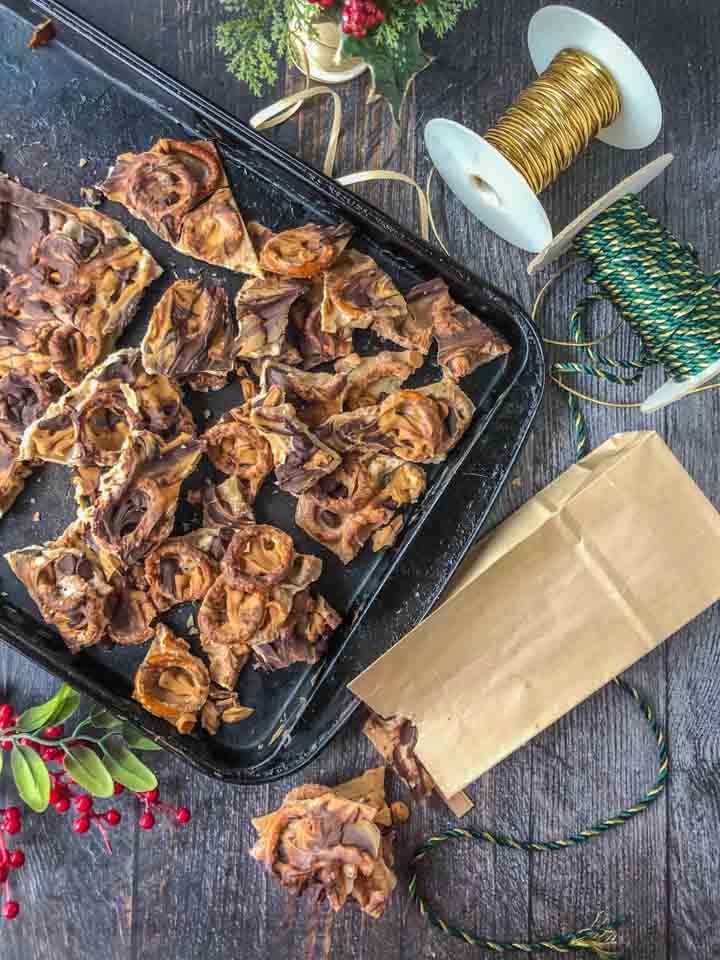pretzel bark on a cookie sheet with ribbons in background with a paper bag