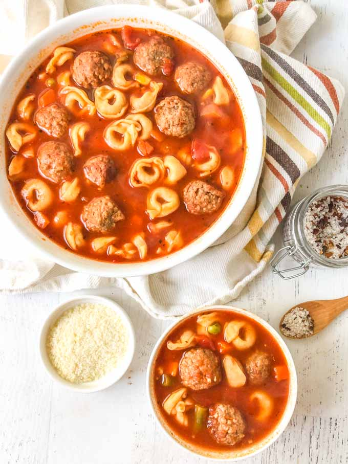 large white bowl with Italian meatball & tortellini soup, sea salt, bowl of parmesan cheese and a small bowl of soup