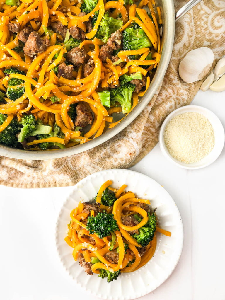a pan and plate with gluten free veggie noodles with parmesan cheese and garlic
