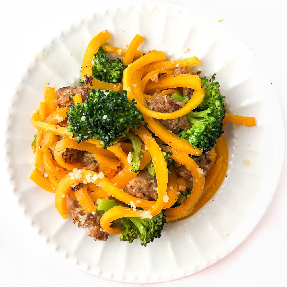 a white plate with butternut squash noodles with sausage and broccoli