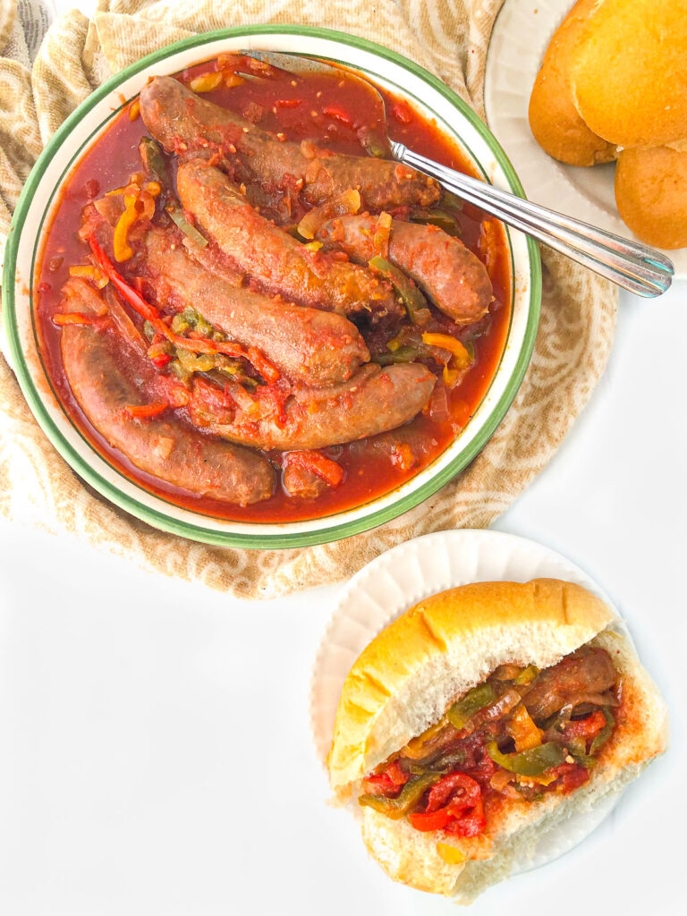 aerial view of a bowl of hot sausage and peppers and a sausage sub sandwich on a white plate