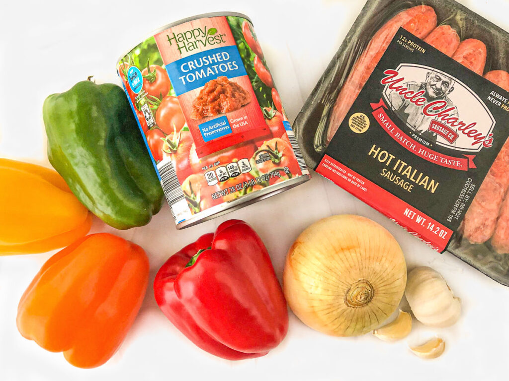 ingredients to make this dish - crushed tomatoes, colorful bell peppers, onions garlic and Italian sausage