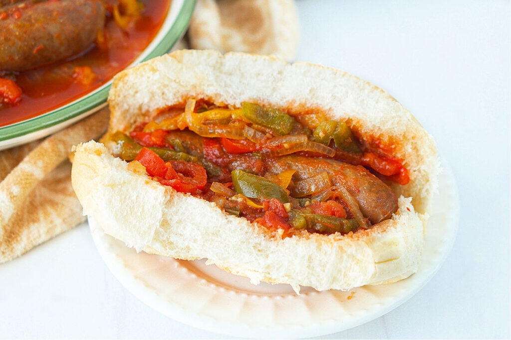 a bun with hot sausage, peppers onions and sauce