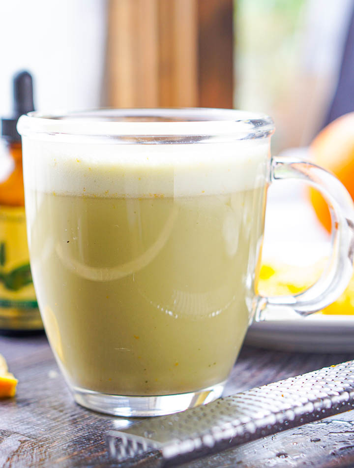 closeup of a clear glass mug with frothy orange creamsicle protein matcha drink and a microwplane
