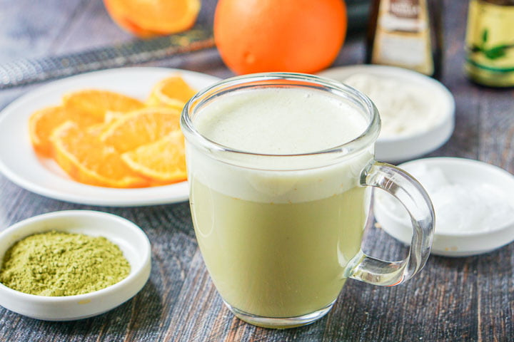 glass mug with matcha green tea protein drink and ingredients in the background