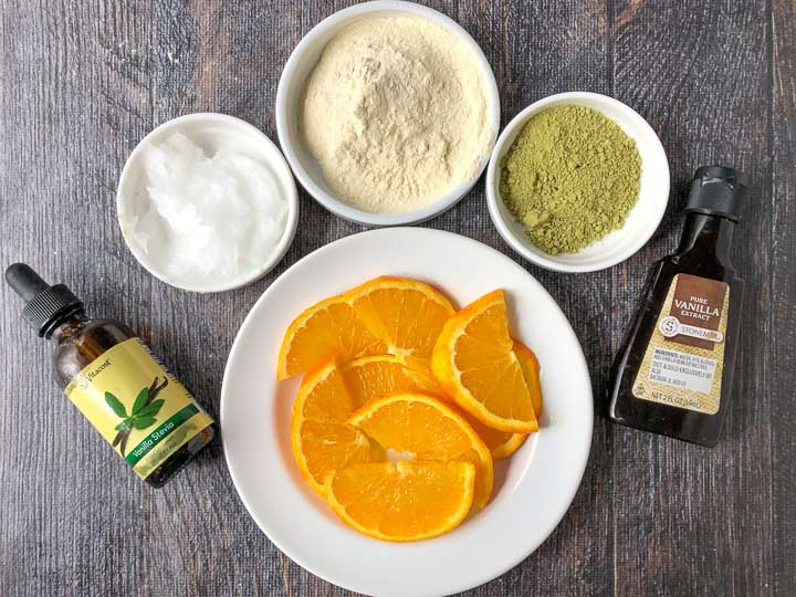 Ingredients to make a creamsicle matcha protein drink: vanilla stevia, orange slices, coconut oil, vanilla protein powder and vanilla extract