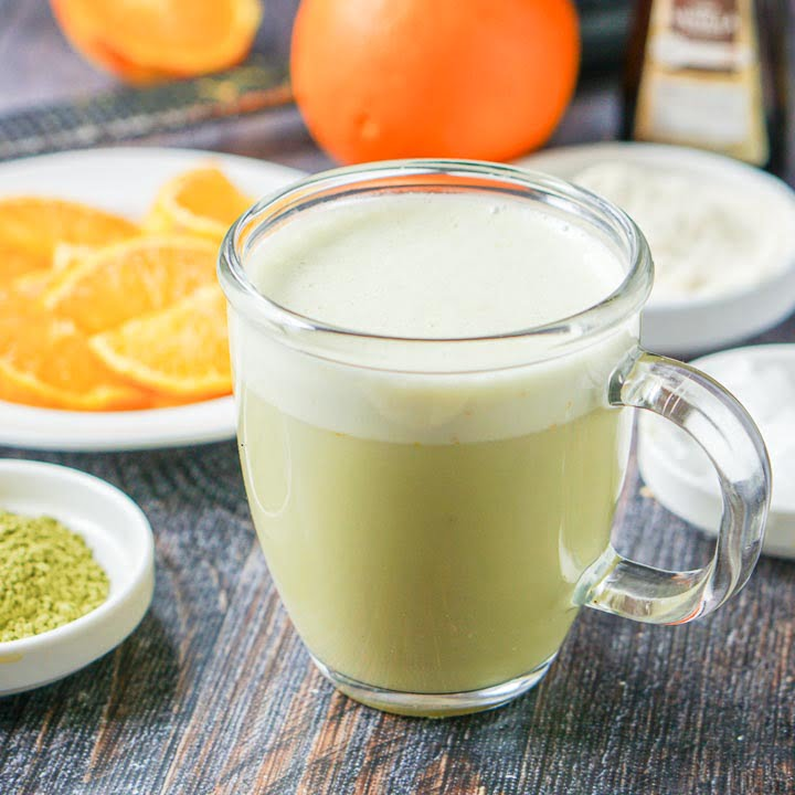 glass mug of low carb orange creamsicle protein matcha drink with bowls of orange slices and matcha in the background