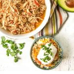 bowls with slow cooker salsa chicken, sprigs of cilantro and text overlay