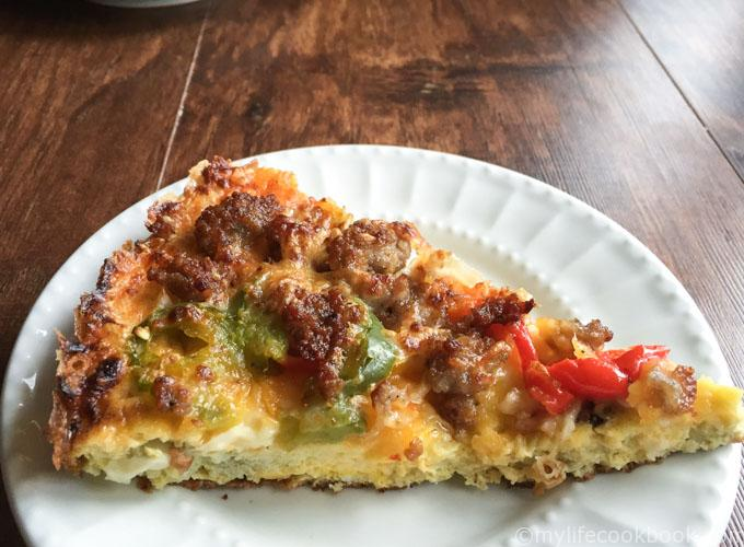 a slice of low carb breakfast pizza on a white plate