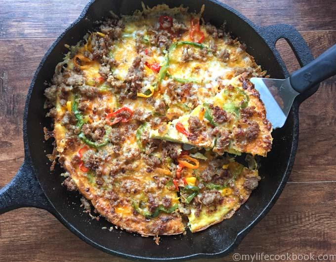 skillet with low carb breakfast pizza with a slice being taken out of