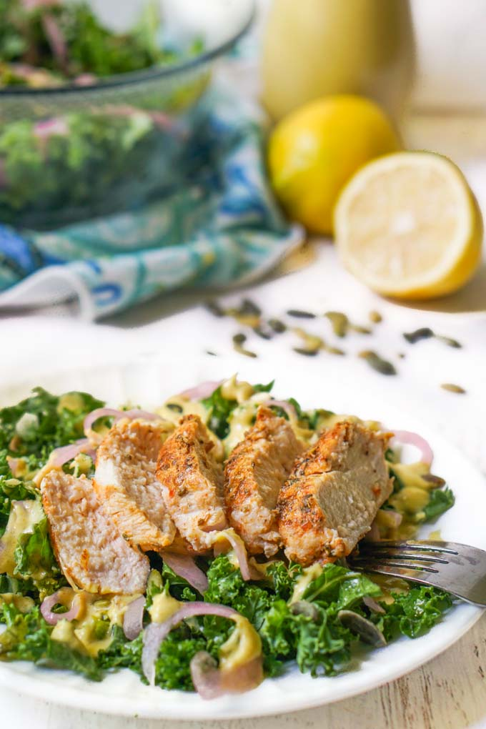 plate of kale salad with chicken breast with dressing and lemons in the background